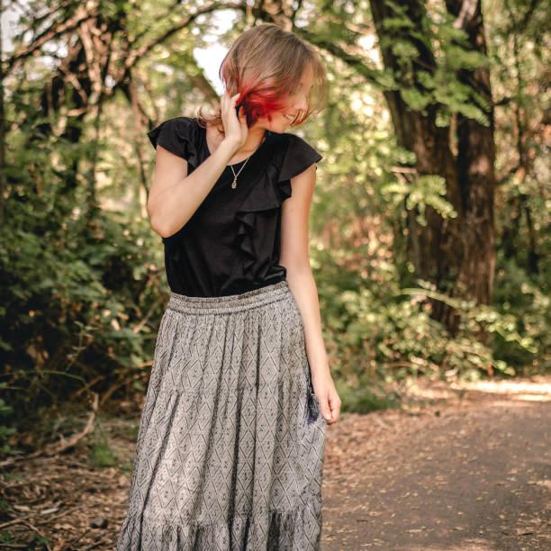 junge frau mit dip-gefärbten roten haaren steht auf einem weg im freien - damen rock braun stock-fotos und bilder