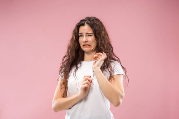 Young woman with disgusted expression repulsing something, isolated on the pink stock photo