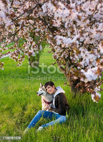 Young woman with dog in the nature on a beautiful spring day.
