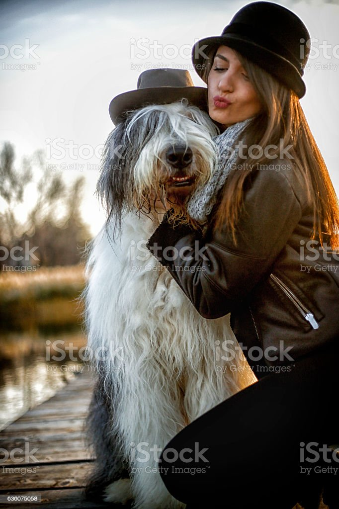 Young woman with dog on pier. Girl kissing her dog stock photo