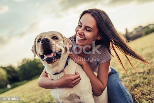 istock Young woman with dog 942616500
