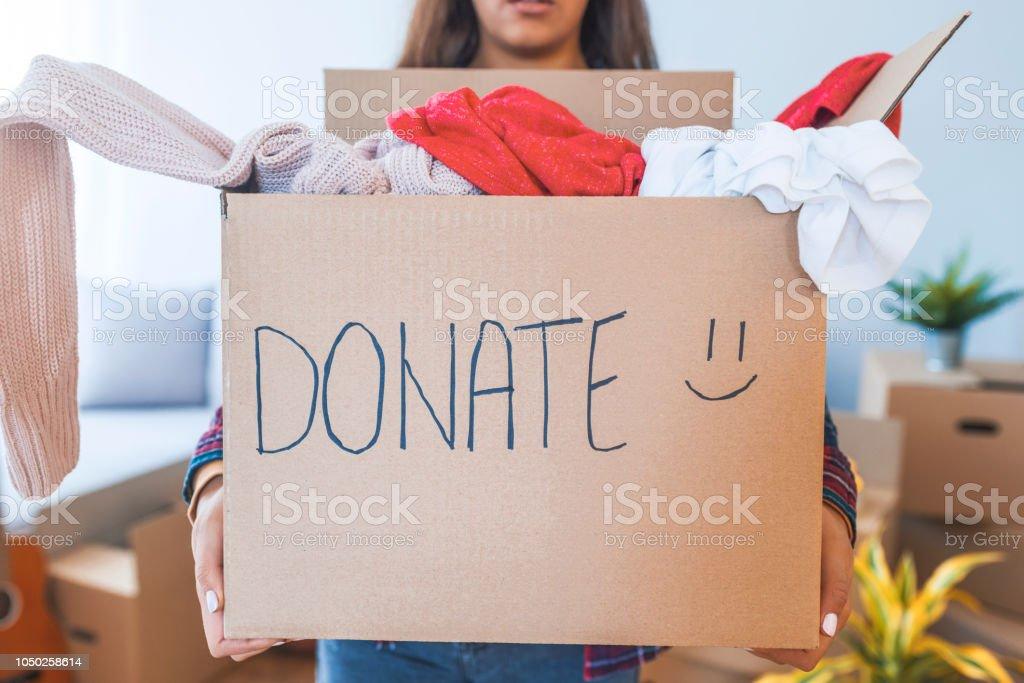 Mujer joven con cuadro de donación en el hogar foto de stock libre de derechos