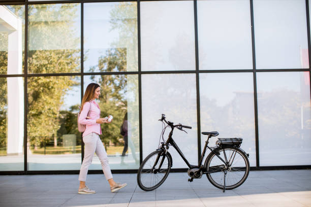 Young woman with ebicycle using on mobile phone stock photo