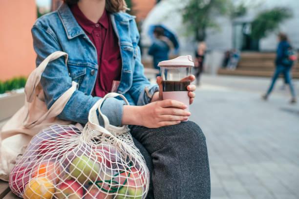 young woman with eco-friendly reusable coffee cup and cotton bag, zero waste concept - riutilizzabile foto e immagini stock