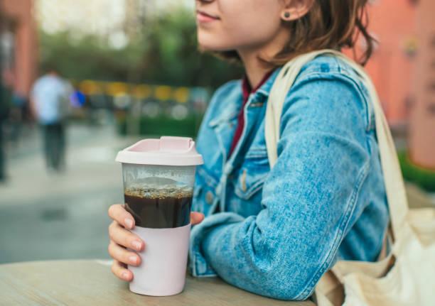 Junge Frau mit umweltfreundlichen wiederverwendbaren Kaffeetasse und Baumwolltasche, Null-Abfall-Konzept – Foto