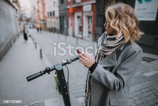 874772840istockphoto Young woman with electric scooter checking her smartphone 1081702862