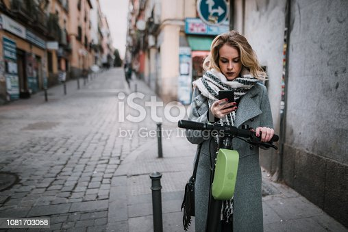 874772840istockphoto Young woman with electric scooter checking her smartphone 1081703058