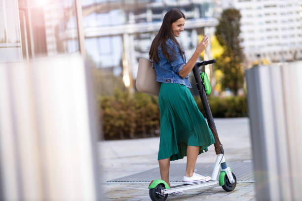Young woman with electric scooter checking her smartphone stock photo