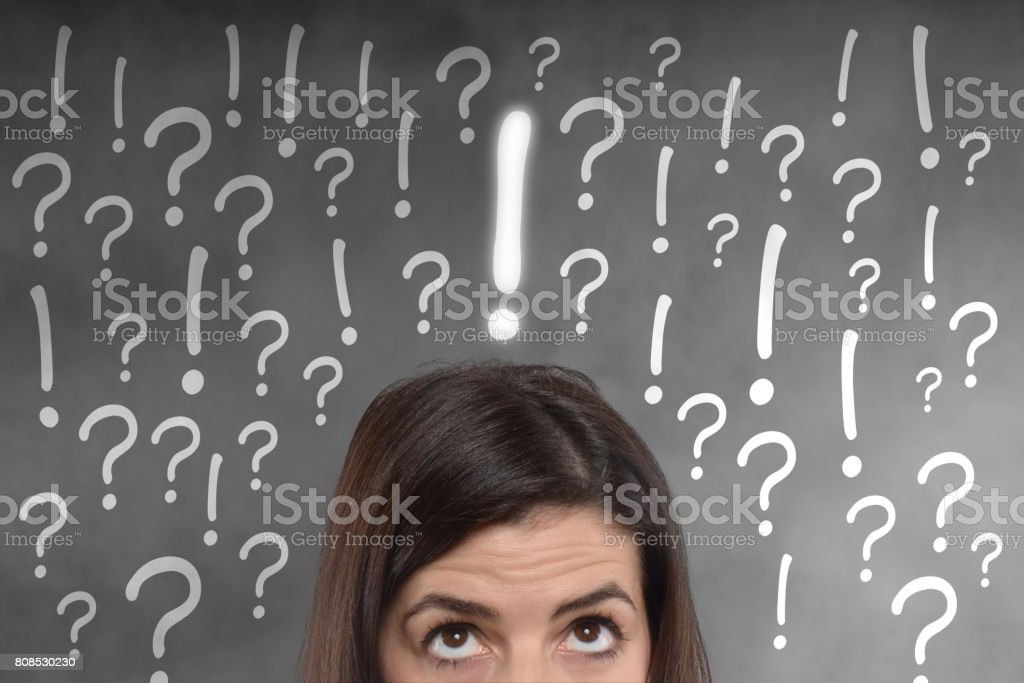 young woman with exclamation and question marks on her head stock photo
