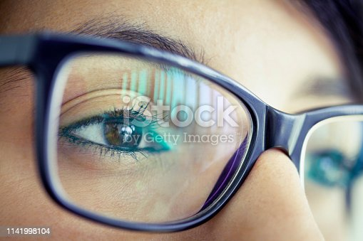 Young woman with eyeglasses, close-up of eye