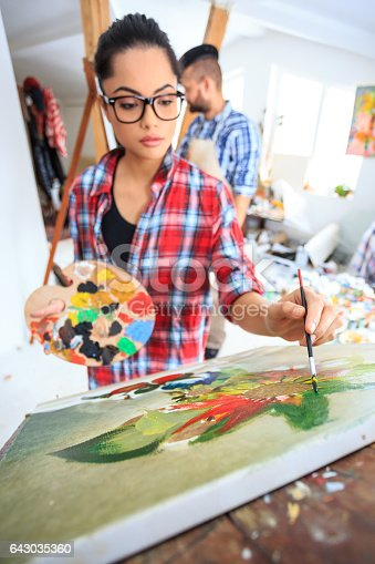 655303558 istock photo Young woman with eyeglasses drawing nature morte in atelier 643035360