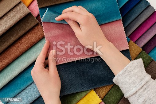 Young woman with fabric samples for curtains at table. Multiple color fabric texture samples selection fabrics for interior decoration. Furniture upholstery