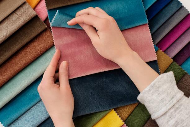 junge frau mit stoffproben für vorhänge am tisch. mehrere farbtexturen, die stoffe für die inneneinrichtung auswählen. möbelpolster - textilien stock-fotos und bilder
