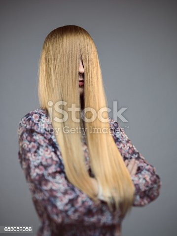 Vertical shot of young woman with face covered by long blonde hair. Real woman standing with arms crossed against gray background. Vertical studio portrait.