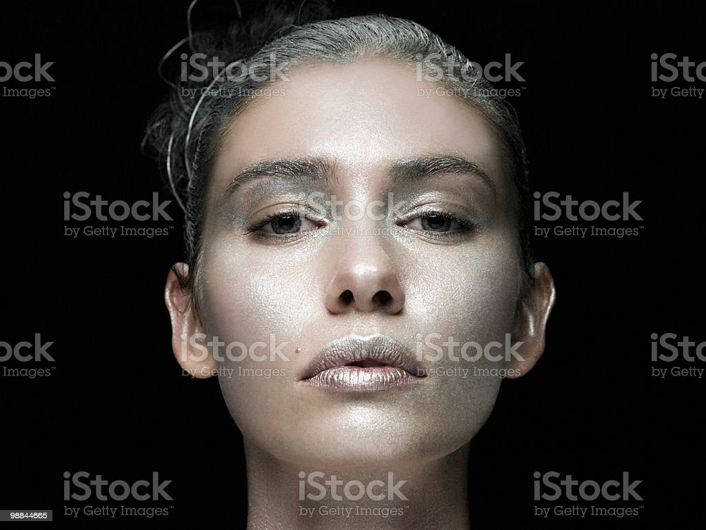 Young woman with face covered in silver make up royalty-free 스톡 사진