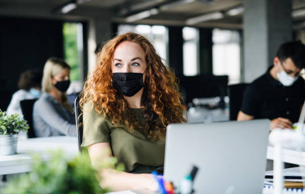 Young woman with face mask back at work in office after lockdown. stock photo