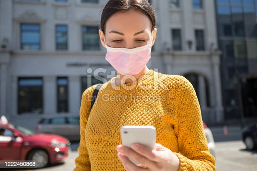 Young Woman With Face Mask Using Smart Phone