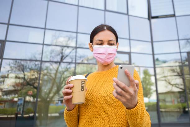 Junge Frau mit Gesichtsmaske vor dem Bürogebäude mit Blick auf Smartphone halten Kaffee – Foto
