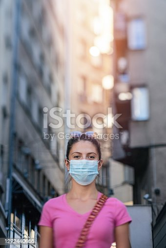 Beautiful young woman wearing protective mask, walking in the city. Tilt-shift lens used