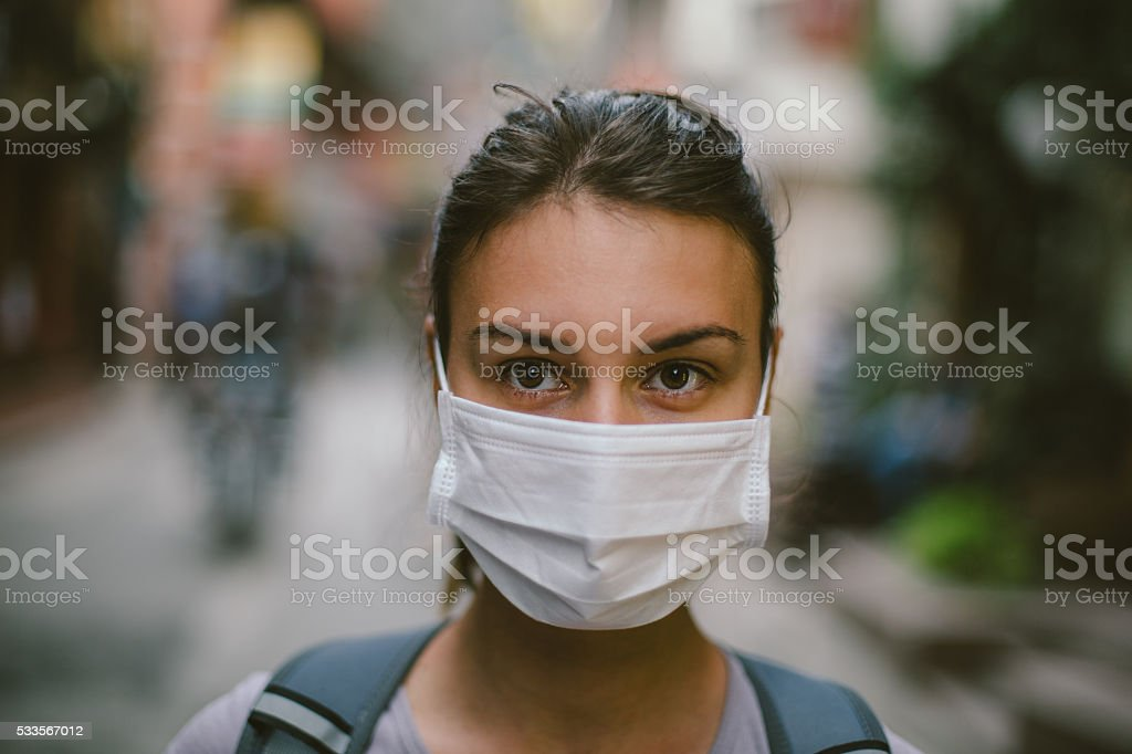 Young woman with face mask in the street stock photo