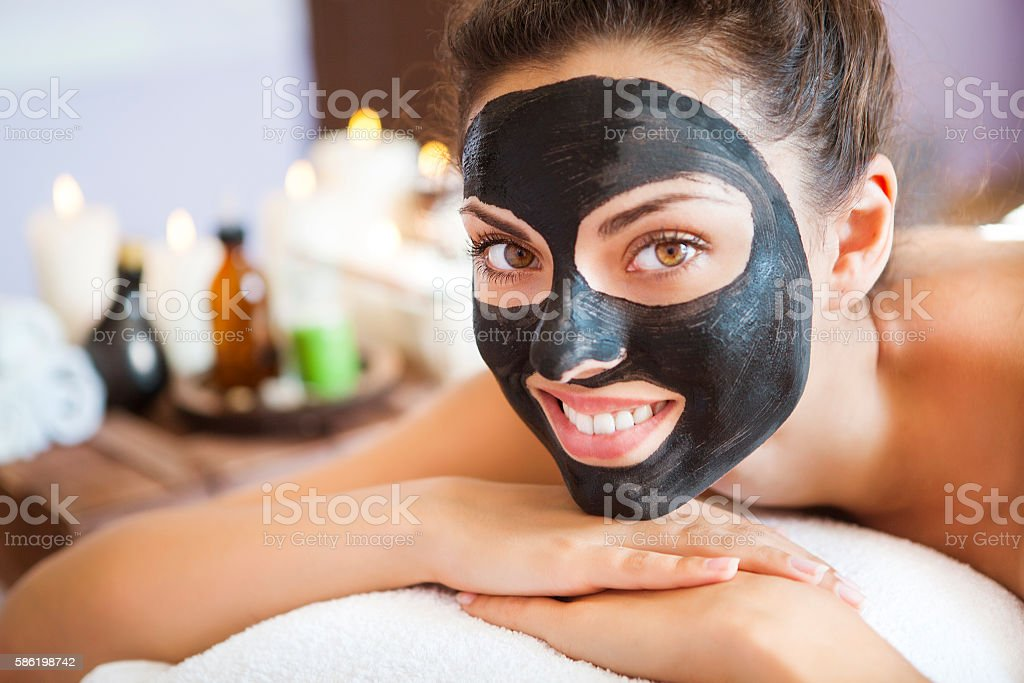 Young woman with face mask of therapeutic black mud stock photo
