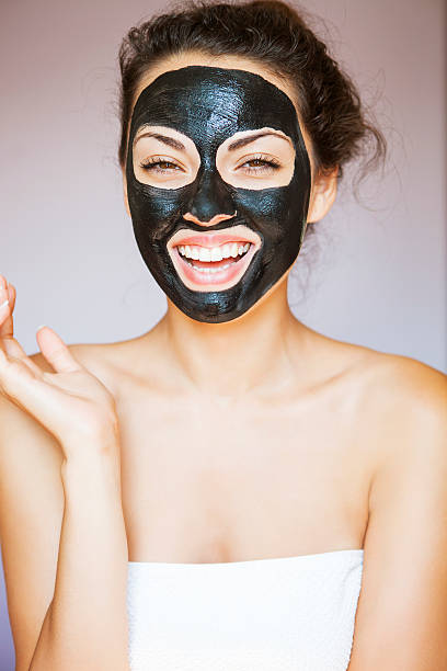 Young woman with face mask of therapeutic black mud - foto stock