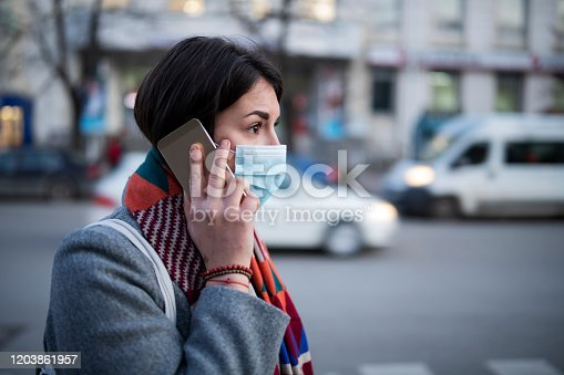 Side view of young woman with face mask walking on the street and talking on the phone.