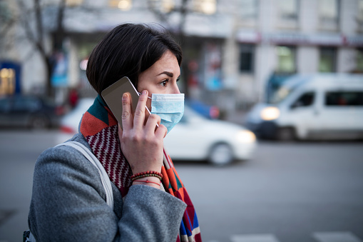 istock Young Woman With Face Mask Talking On The Phone. 1203861957