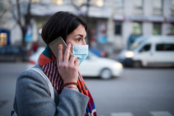 young woman with face mask talking on the phone. - covid mask stock pictures, royalty-free photos & images