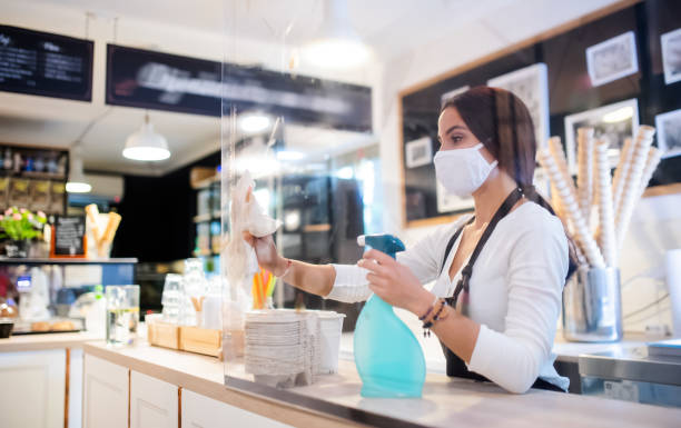 Young woman with face mask working indoors in cafe, disinfecting counter. stock photo