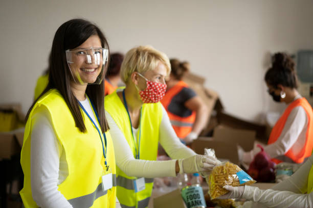 Young woman with face shield helping her colleagues collecting food for donation stock photo