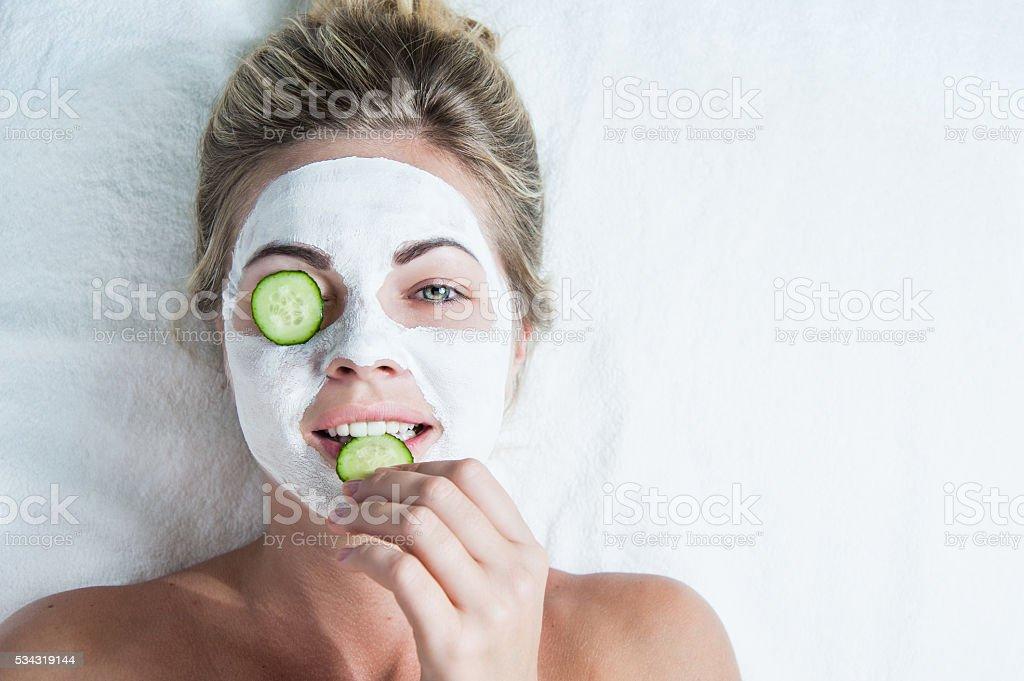 Junge Frau mit Gesichtsmaske, beißen auf eine Gurke – Foto