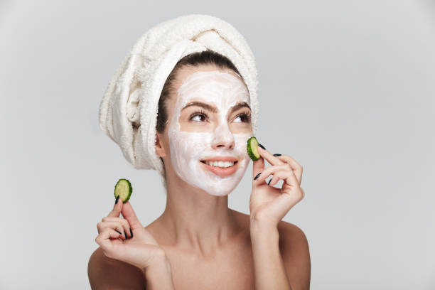 young woman with facial skincare mask and cucumber slices isolated on white - maschera foto e immagini stock