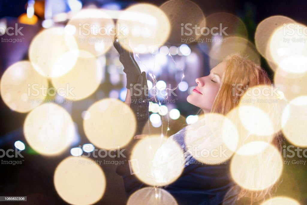 Young woman with fairy lights in cold city night imagine about...