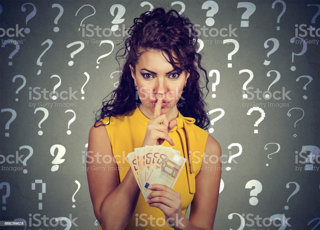 Young woman with finger on lips gesture and euro banknotes in hand stock photo