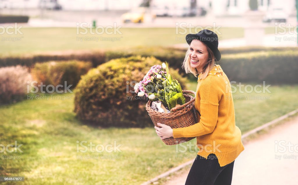 Young woman with flowers in a basket in sunny spring town. royalty-free stock photo
