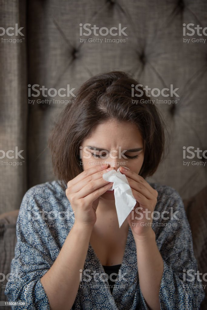 Young woman holds a napkin and cleans her nose. She is at home in her...