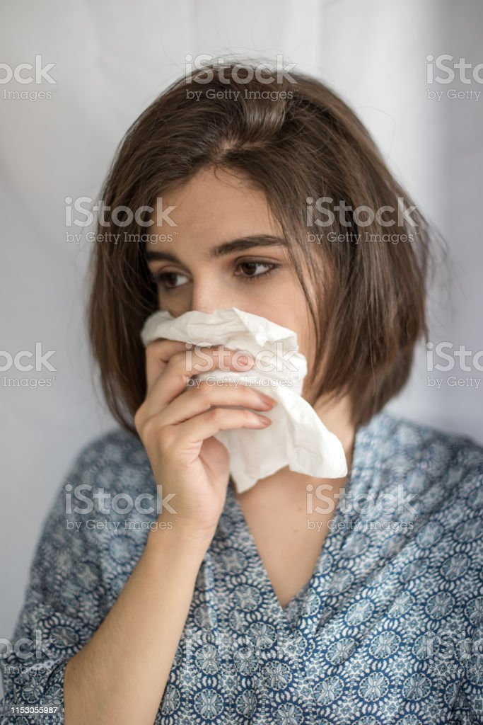 Young woman holds a napkin and cleans her itchy eyes and nose. She...