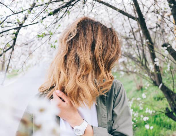 junge frau mit flatternden blonde haare stehen - vogue muster stock-fotos und bilder