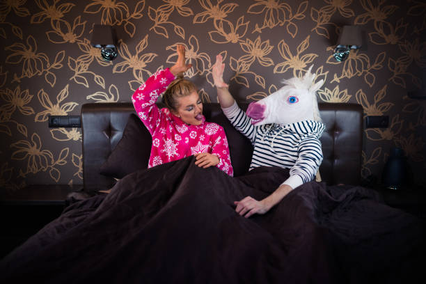 young woman with freaky man in comical mask - unicorn bed imagens e fotografias de stock