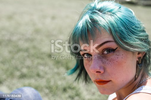 Beautiful young woman with dyed blue hair and red lipstick portrait.