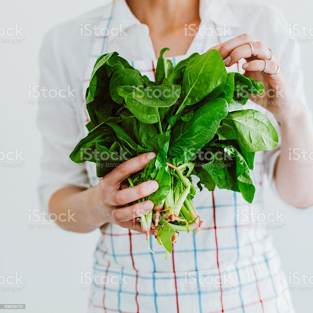 Young woman with fresh spinach stock photo