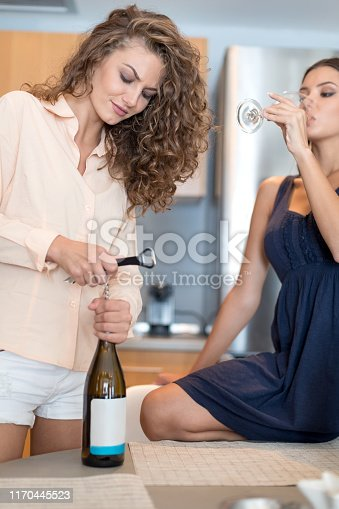 Young woman opening wine bottle with corkscrew on dining table by her friend drinking wine