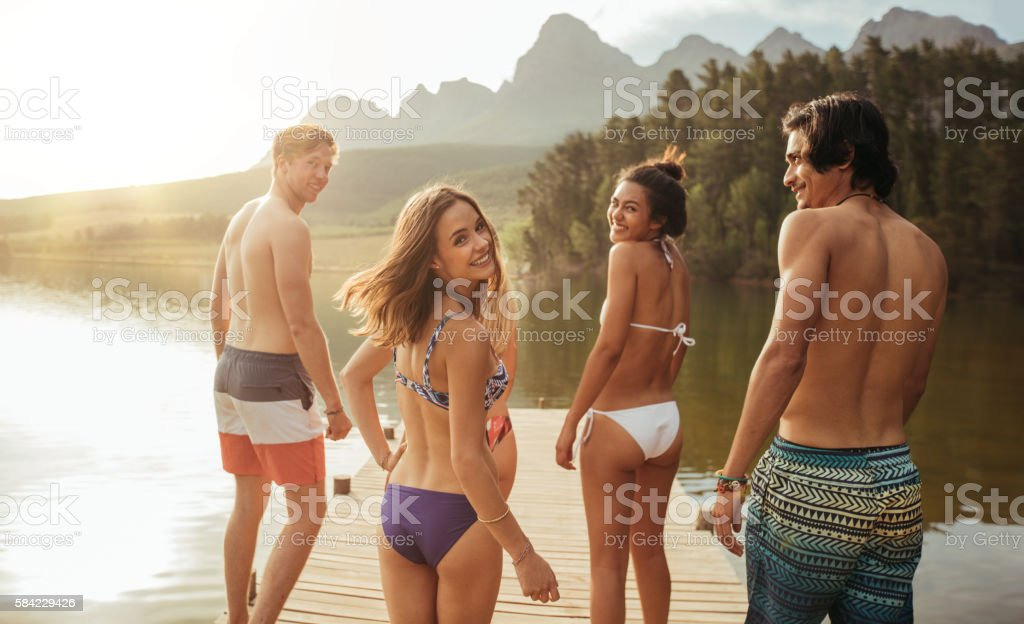 Young woman with friends and walking on the jetty stock photo