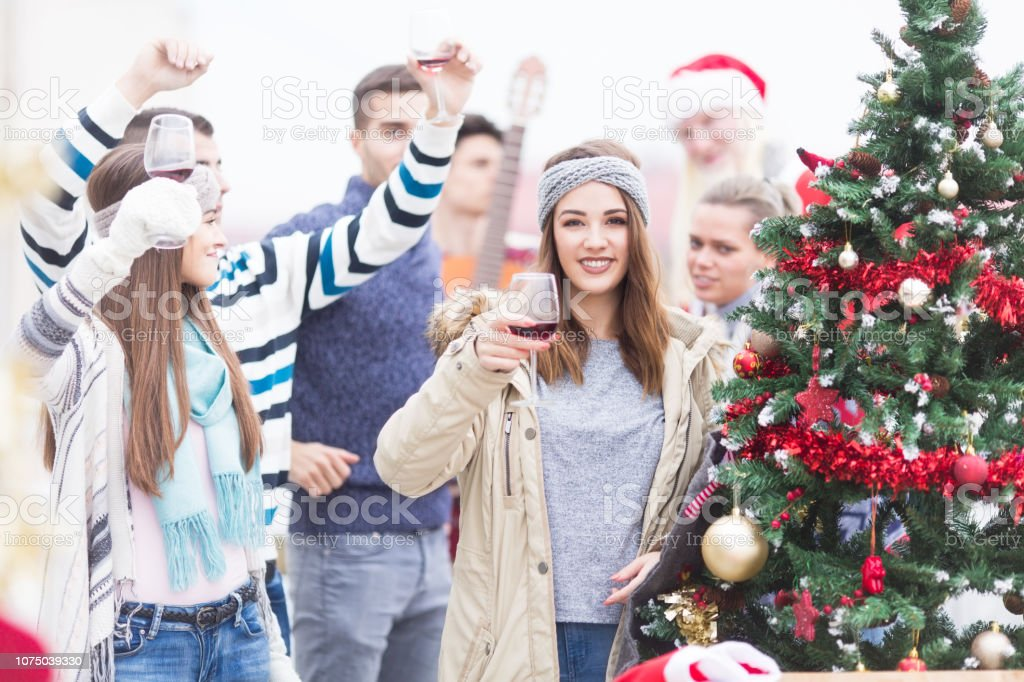 Young woman with friends on balcony celebrating Christmas stock photo