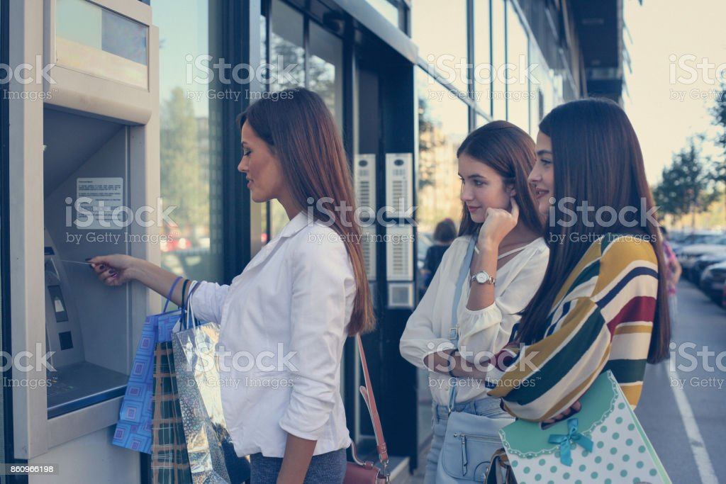 Young woman with friends take money from cash machine. stock photo