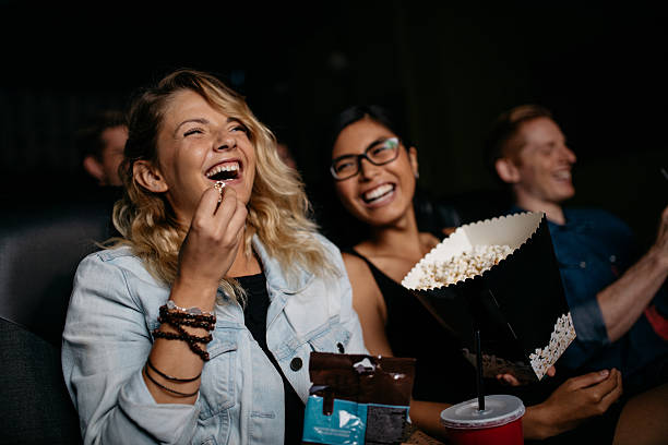 Young woman with friends watching movie stock photo