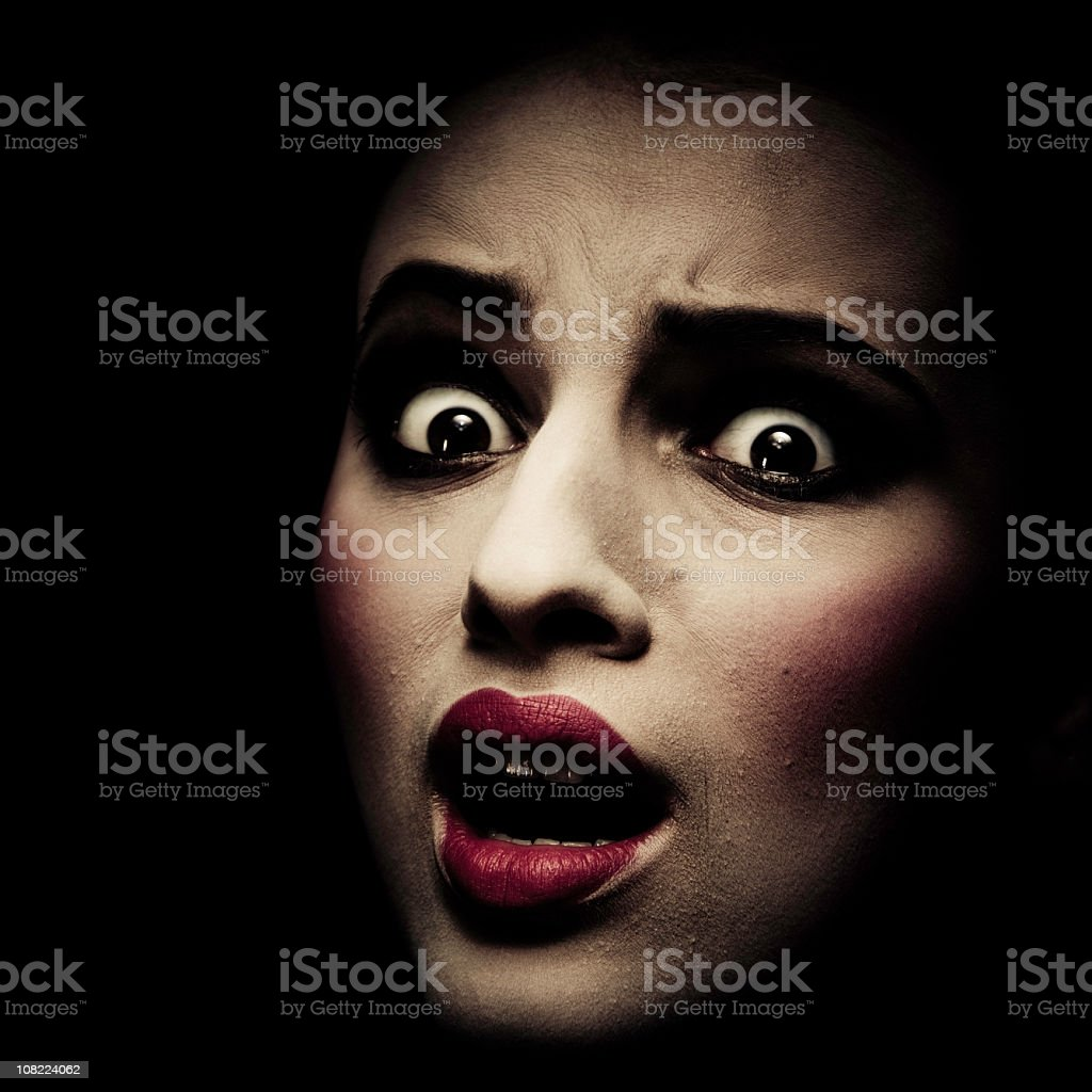 Young woman with frightened look, low key stock photo