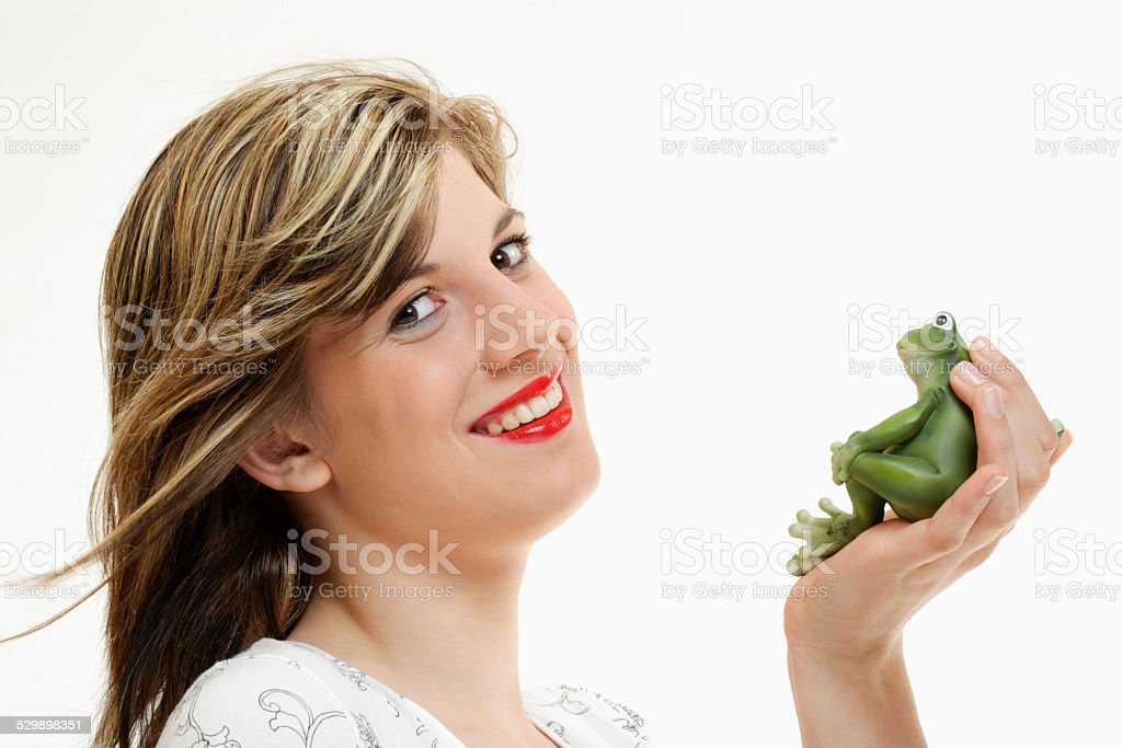 Young woman with frog figure in her hand stock photo