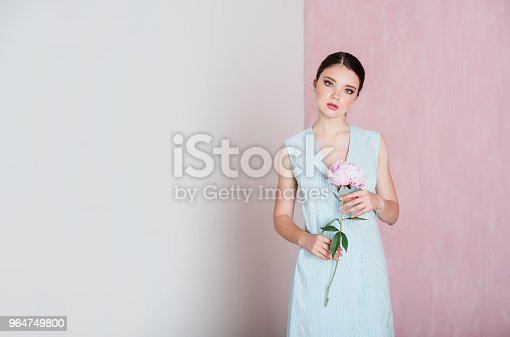 A Young Woman With Gathered Hair Is Standing Holding A Peony In Her Hands Stock Photo & More Pictures of Adult
